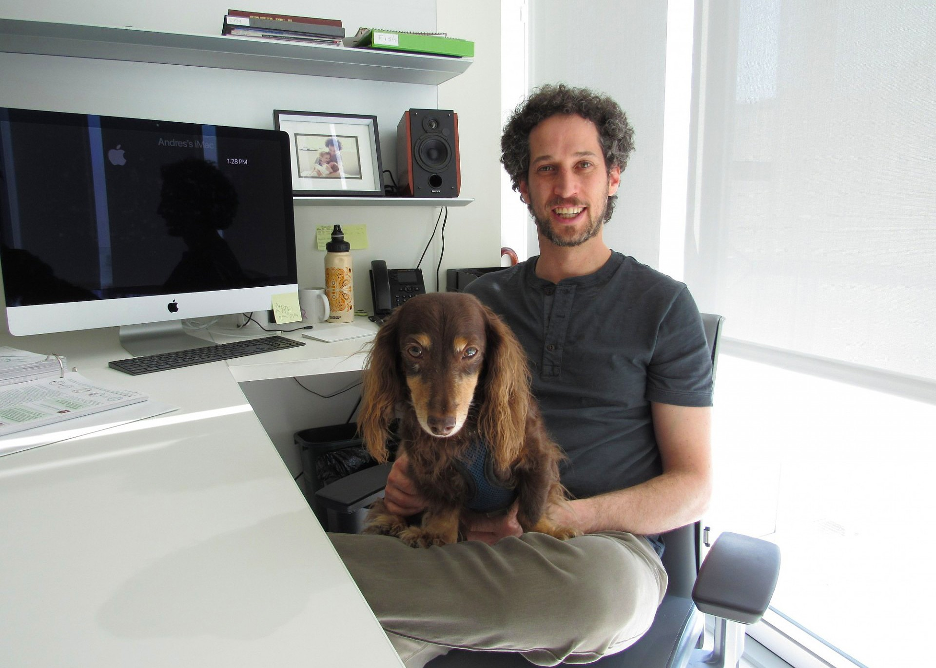Andres Bendesky in lab with dog in his lap.